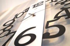 ρολόι ανασκόπησης που απομονώνεται πέρα από το λευκό τοίχων Στοκ Φωτογραφίες