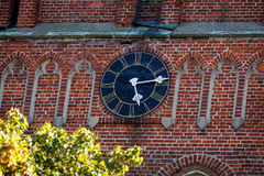 Ρολόι εκκλησιών στο τούβλινο υπόβαθρο Στοκ φωτογραφίες με δικαίωμα ελεύθερης χρήσης