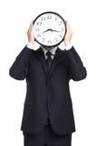 Ρολόι εκμετάλλευσης επιχειρηματιών μπροστά από το πρόσωπό του στοκ εικόνες