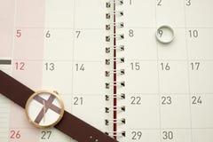 Ρολόι και ασημένιο δαχτυλίδι που τίθενται στο ημερολόγιο υπολογιστών γραφείου Στοκ φωτογραφία με δικαίωμα ελεύθερης χρήσης