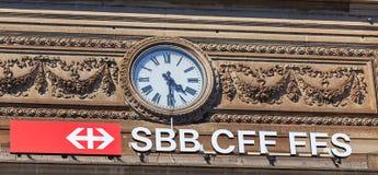 Ρολόι και το σημάδι των ελβετικών ομοσπονδιακών σιδηροδρόμων στην πρόσοψη ο Στοκ Εικόνα