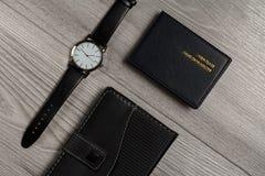 Ρολόι με ένα λουρί δέρματος, σημειωματάριο, κάτοχος καρτών ονόματος σε έναν γκρίζο Στοκ Εικόνα