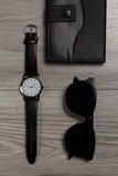 Ρολόι με ένα λουρί δέρματος, σημειωματάριο, μαύρα γυαλιά ηλίου σε έναν γκρίζο Στοκ εικόνα με δικαίωμα ελεύθερης χρήσης