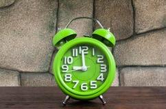 Ρολόι στο ξύλινο πάτωμα με το πέτρινο υπόβαθρο Στοκ Εικόνα