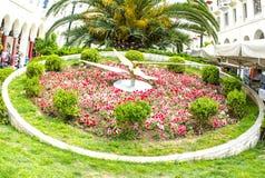 ρολόι στο πάρκο με τα κόκκινα λουλούδια Στοκ φωτογραφία με δικαίωμα ελεύθερης χρήσης