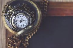 2 ρολόι τσεπών με την αλυσίδα στο μαύρο πίνακα με κενό Spac Στοκ Εικόνες