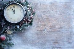 Ρολόι Χριστουγέννων πέρα από το ξύλινο υπόβαθρο χιονιού. στοκ φωτογραφία