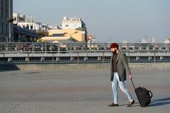 Ρυθμίστε τη διαβίωση στη νέα πόλη Φέρτε την τσάντα ταξιδιού Γενειοφόρο ταξίδι hipster ατόμων με την τσάντα αποσκευών στις ρόδες Τ στοκ φωτογραφία με δικαίωμα ελεύθερης χρήσης