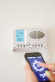 Ρυθμίστε τη θερμοκρασία στο εγχώριο εσωτερικό με το smartphone στοκ φωτογραφία με δικαίωμα ελεύθερης χρήσης
