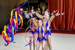 Ρυθμικές πράξεις γυμναστικής ομάδας με τις κορδέλλες Στοκ Φωτογραφίες