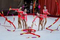 Ρυθμικές πράξεις γυμναστικής ομάδας με τις κορδέλλες Στοκ Εικόνες