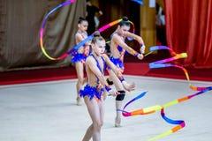 Ρυθμικές πράξεις γυμναστικής ομάδας με τις κορδέλλες Στοκ εικόνες με δικαίωμα ελεύθερης χρήσης