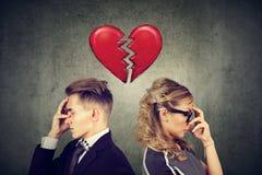 Ρωγμή στις σχέσεις Λυπημένο ζεύγος που στέκεται πλάτη με πλάτη με τη σπασμένη καρδιά ενδιάμεσα Στοκ φωτογραφία με δικαίωμα ελεύθερης χρήσης