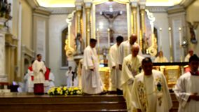 Ρωμαίος - καθολικοί παπάδες που έχουν μια κοιλότητα πορείας μετά από τη μάζα κοινοτήτων θαμπάδες απόθεμα βίντεο