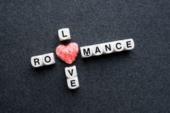 Ρωμανικό κείμενο φραγμών σταυρόλεξων αγάπης με τη ρόδινη καρδιά νημάτων στο σκοτάδι Στοκ Εικόνες