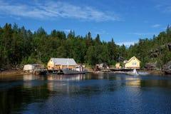 Ρωσία, φιορδ στο άσπρο αυστηρό βόρειο τοπίο παραλιών με ένα χαρακτηριστικό ψαροχώρι στο βόρειο τμήμα της Ρωσίας Ο μικρός Βορράς Στοκ Φωτογραφίες