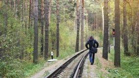 Ρωσία, Novosibirsk, στις 5 Οκτωβρίου 2016, μόνο άτομο που περπατά στο δρόμο σιδηροδρόμων στο βαθύ πεύκο δασικό 3840x2160 απόθεμα βίντεο