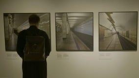 ΡΩΣΙΑ, ΜΟΣΧΑ - 10 ΙΟΥΝΊΟΥ 2017: Άτομο στο δωμάτιο στοών που εξετάζει τα πλαίσια εικόνων Επιχειρηματίας στο κοίταγμα γκαλεριών τέχ Στοκ Φωτογραφίες