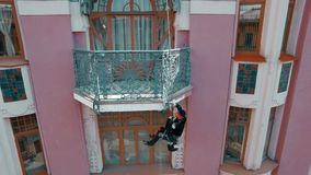 ΡΩΣΙΑ ST PETERBURG- 22 ΑΠΡΙΛΊΟΥ: εναέρια άποψη του ζωγράφου που κρεμά σε ένα σχοινί και τα χρώματα την πρόσοψη ενός ιστορικού κτη απόθεμα βίντεο