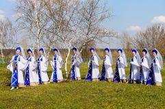 Ρωσικά κορίτσια στο στρογγυλό χορό sundresses των σημύδων στοκ φωτογραφία