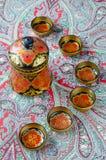 Ρωσικά παραδοσιακά πιάτα Khokhloma σε ένα κόκκινο χαρτομάνδηλο Στοκ Φωτογραφία