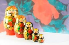 Ρωσικά matryoshkas σε ένα ελαφρύ υπόβαθρο και ένα χρωματισμένο υπόβαθρο Στοκ Εικόνες