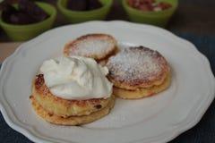 Ρωσικές γλυκές τηγανίτες τυριών με την ξινή κρέμα για το πρόγευμα ή ένα πρόχειρο φαγητό Στοκ εικόνα με δικαίωμα ελεύθερης χρήσης
