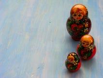 Ρωσικές να τοποθετηθεί Matrioshka Matryoshka κουκλών κούκλες στο μπλε ξύλινο υπόβαθρο με το διάστημα αντιγράφων Στοκ Φωτογραφίες