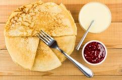 Ρωσικές τηγανίτες στο πιάτο, κύπελλα με τη μαρμελάδα σμέουρων, δίκρανο Στοκ Φωτογραφία