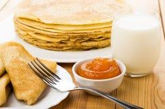 Ρωσικές τηγανίτες στο πιάτο, το γάλα και το κύπελλο με τη μαρμελάδα ροδάκινων Στοκ φωτογραφία με δικαίωμα ελεύθερης χρήσης
