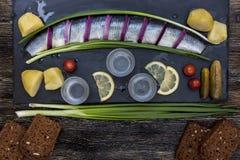 Ρωσική γιορτή με τις ρέγγες, τα κρεμμύδια, τις πατάτες και τη βότκα Στοκ Φωτογραφίες