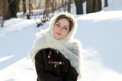 Ρωσική ομορφιά σε ένα άσπρο πλεκτό μαντίλι στο χιόνι Στοκ φωτογραφία με δικαίωμα ελεύθερης χρήσης
