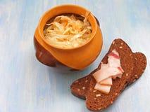Ρωσική παραδοσιακή κουζίνα: Sauerkraut σε ένα κεραμικό δοχείο βαρελιών με το σπάσιμο και λαρδί στο μπλε υπόβαθρο στοκ εικόνα