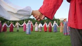 Ρωσικός λαϊκός χορός ομάδας κύκλων - άνδρες και γυναίκα στο εθνικό λαϊκό κοστούμι υπαίθριο απόθεμα βίντεο