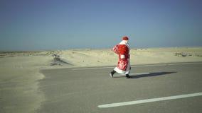 Ρωσικό Άγιος Βασίλης ή Ded Moroz με τους περιπάτους σάκων στην άμμο, βρήκε το δρόμο ασφάλτου στην έρημο, έρχεται, ερχόμενος στην  απόθεμα βίντεο