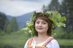 Ρωσικό κορίτσι με μια ανθοδέσμη των λουλουδιών στο κεφάλι της Στοκ Εικόνα