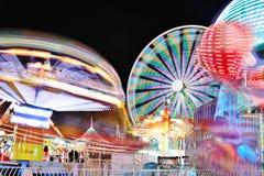 Ρόδα καρναβαλιού και Ferris τη νύχτα - φωτεινά φω'τα και μακροχρόνια έκθεση Στοκ Εικόνα