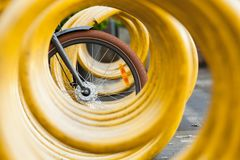 Ρόδα ποδηλάτων και κίτρινος σπειροειδής χώρος στάθμευσης ποδηλάτων Στοκ φωτογραφία με δικαίωμα ελεύθερης χρήσης