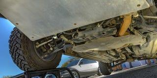 Ρόδα σε έναν φραγμό που παρουσιάζει κάτω από τα πλαίσια ενός αυτοκινήτου στοκ φωτογραφία με δικαίωμα ελεύθερης χρήσης