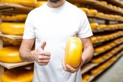 Ρόδα τυριών εκμετάλλευσης στην αποθήκευση στοκ φωτογραφίες