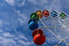 Ρόδα Ferris ενάντια στο μπλε ουρανό με τα άσπρα σύννεφα Στοκ Εικόνες
