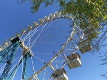 Ρόδα Ferris ενάντια στο φωτεινό μπλε ουρανό και πράσινος στοκ φωτογραφίες με δικαίωμα ελεύθερης χρήσης