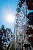 Ρόδα Ferris στις ακτίνες υποβάθρου και ήλιων μπλε ουρανού που δίνουν ένα έντονο φως Στο λούνα παρκ Το Σαββατοκύριακο Στοκ φωτογραφία με δικαίωμα ελεύθερης χρήσης