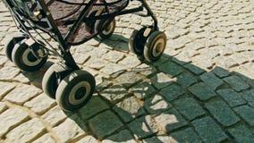 Ρόδες ενός περιπατητή που κυλά Cobble στον πέτρινο δρόμο στοκ εικόνα