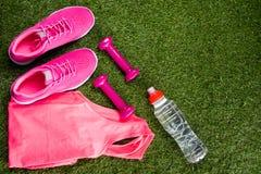Ρόδινα αθλητικά πάνινα παπούτσια και μια μπλούζα, για την ικανότητα, ένα μπουκάλι νερό και αλτήρες, στο υπόβαθρο της χλόης με στοκ φωτογραφία με δικαίωμα ελεύθερης χρήσης