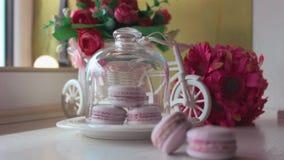 Ρόδινα γαλλικά macarons κάτω από το γυαλί στους ξύλινους πίνακες, μαλακό υπόβαθρο εστίασης Γλυκιά έρημος στον καφέ απόθεμα βίντεο