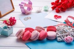 Ρόδινα διαμορφωμένα καρδιά macaroons και γαμήλια δαχτυλίδια με την κάρτα, πλαίσιο φωτογραφιών Στοκ Εικόνες