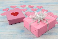 Ρόδινα λαμπρά καρδιές και κιβώτια δώρων σε ένα μπλε ξύλινο υπόβαθρο βαλεντίνος ημέρας s στοκ φωτογραφία με δικαίωμα ελεύθερης χρήσης