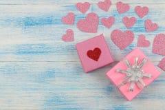 Ρόδινα λαμπρά καρδιές και κιβώτια δώρων σε ένα μπλε ξύλινο υπόβαθρο επάνω από την όψη τοποθετήστε το κείμενο βαλεντίνος ημέρας s στοκ εικόνα με δικαίωμα ελεύθερης χρήσης
