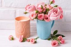 Ρόδινα λουλούδια τριαντάφυλλων στο μπλε φλυτζάνι και το καίγοντας κερί Στοκ Φωτογραφία
